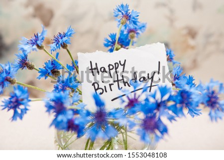 Happy birthday card with greeting words and bouquet of blue cornflower flowers