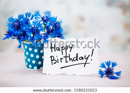 Happy birthday card with lettering and blue cornflower flowers, anniversary celebration with bouquet