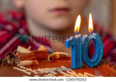 Happy 10 birthday celebration . Chocolate cake and blue candles. Image not in focus.