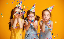 happy birthday children girls with confetti on  colored yellow background
