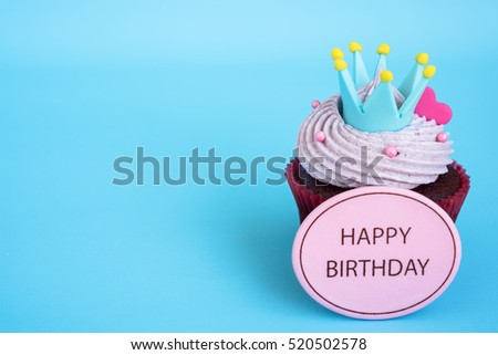 Happy birthday cupcake with crown and pink heart over blue background with copy space, Gift for birthday
