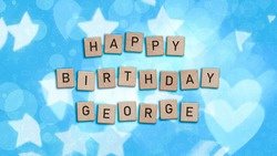 Happy Birthday George card with wooden tiles text. Boys birthday card in blue.