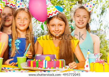 Happy birthday girl in party hat among her friends #495772045