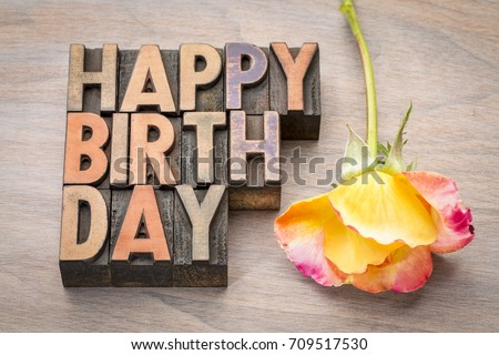 Happy Birthday greeting card in vintage letterpress wood type against grained wood with a rose