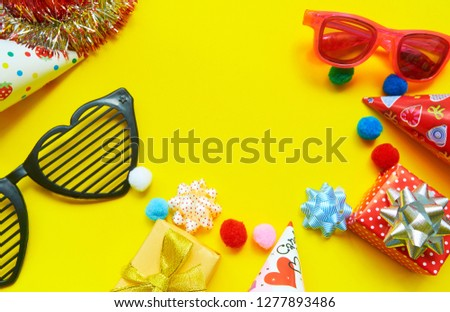 Happy birthday greeting card with gift box, glasses, party hats on yellow background with copy space #1277893486