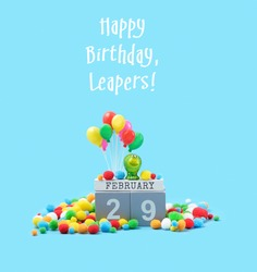 Happy Birthday, Leapers greeting card. February 29 date calendar, Frog, festive decor, balloons on blue background. leap day in leap year concept.