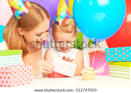 happy birthday. mother giving a gift to his little daughter with balloons and cake