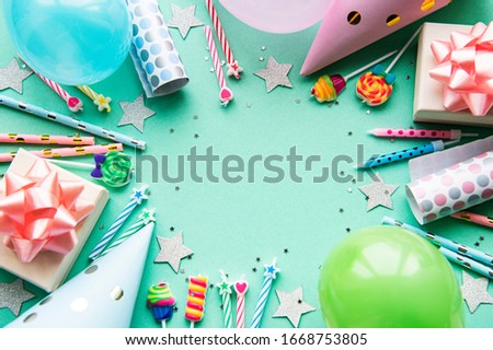 Happy birthday or party background.  Flat Lay wtih birthday balloons , confetti and ribbons on pastel green background. Top View.  Copy space.