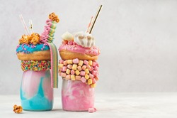 Happy Birthday party background: Two freak shakes topping with donut, marshmallow, meringues, popcorn and marmalade over grey background with copy space; selective focus.