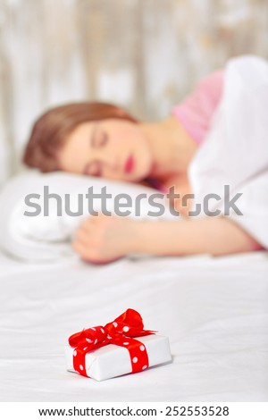 Happy birthday. Portrait of a beautiful young woman sleeping in bed having a birthday gift on her pillow with selective focus