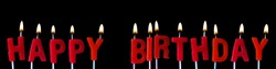Happy Birthday spellt out in red candles against a black background