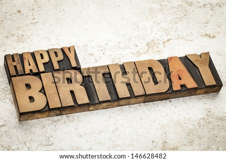 happy birthday text  in vintage letterpress wood type on a ceramic tile background