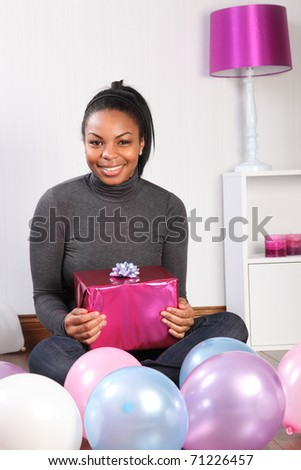 Happy birthday. Time to celebrate for beautiful, smiling young African-American girl, sitting on the wood floor at home, with a birthday present, surrounded by balloons. - stock photo