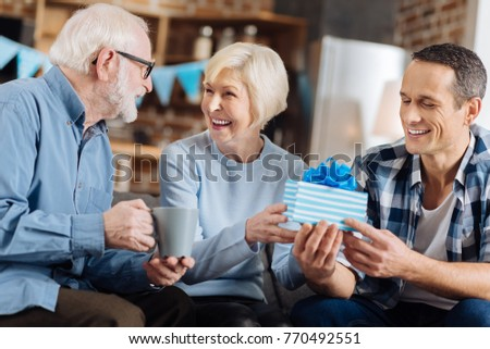 Happy birthday. Upbeat young man sitting on the sofa next to his elderly parents and giving a birthday present to his mother while she sharing happiness with her husband