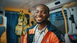Happy Black African American Paramedic Smiles and Poses for Camera in an Ambulance Vehicle with an Injured Patient. Emergency Medical Technician is Cheerful at Work.