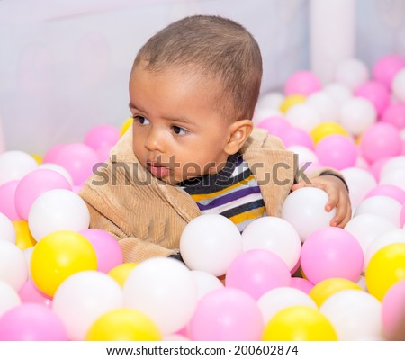 Happy black boy in colored ball on birthday on playground. The concept of childhood and holiday