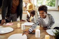 Happy black boy setting dining table while having lunch with his family on holidays.