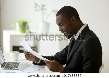 Happy black businessman in suit reading mail letter excited by good news sitting at office desk, african american entrepreneur glad to receive positive answer loan approval in notice notification