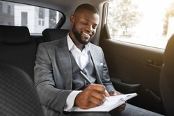 Happy black businessman sitting in car, taking notes. Young african american successful smiling manager making business plan in notepad while going to business meeting by car, empty space