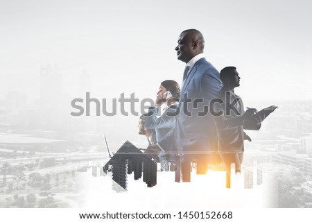 Happy black businessman with other people working in office on cityscape background