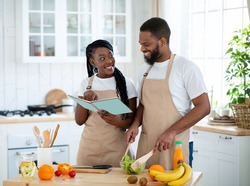 Happy Black Couple Checking Recipe In Cookbook While Preparing Healthy Food Together In Kitchen. Cheerful Young African American Spouses Cooking Vegetarian Meal For Lunch At Home, Free Space