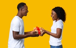 Happy black couple giving Valentine gifts to each other, yellow studio background, free space. Loving african american man giving present to his excited wife or girlfriend, Valentine celebration