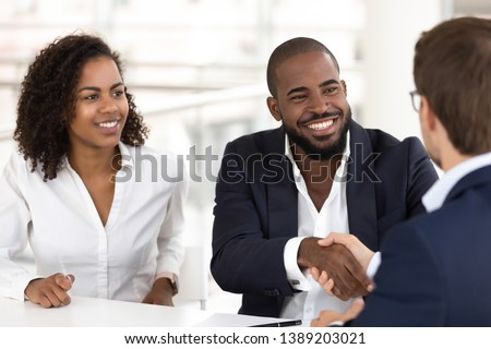 Happy black couple handshake meeting with realtor or real estate agent for consultation, excited african American husband and wife shake hand get acquainted with banker take property loan together