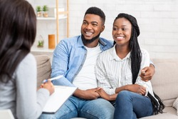 Happy black couple sitting in counselor's office after successful marital therapy, copy space