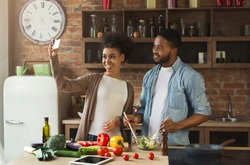 Happy black couple taking photo with smartphone while preparing healthy salad at kitchen