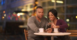 Happy Black couple using smart phone in coffee shop at night