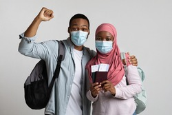 Happy black couple young man and woman in hijab ready to travel abroad during COVID-19 pandemic, wearing protective face masks, holding passports and flight tickets, gray studio background