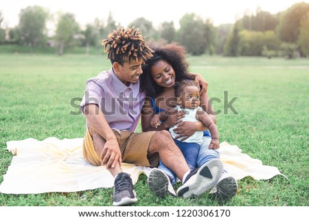 Happy black family doing a picnic outdoor - Mother and father having fun with their daughter in a park - Love and happiness concept