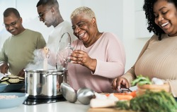 Happy black family having fun cooking together in modern kitchen - Food and parents unity concept