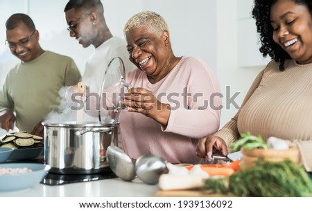 Happy black family having fun cooking together in modern kitchen - Food and parents unity concept  Stockfoto ©