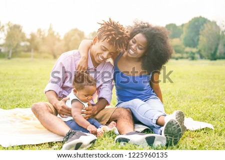 Happy black family having fun doing picnic outdoor - Parents and their daughter enjoying time together in a weekend day - Love tender moments and happiness concept - Focus father and mother on faces