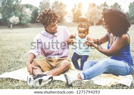 Happy black family having fun doing picnic outdoor - Parents and their daughter enjoying time together in a weekend day - Love tender moments and happiness concept - Focus on child face