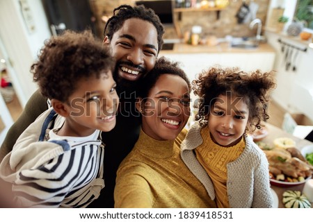 Happy black family having fun on Thanksgiving while taking selfie in dining room.