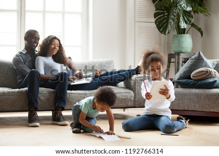 Happy black family spend free time together in living room at home. Couple sitting on sofa looks at little daughter show her drawing, son have a fun on warm wooden floor drawing with colorful pencils