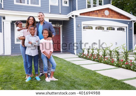 Happy black family standing outside their house