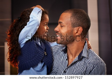 Happy black father and cute little daughter embracing, smiling.