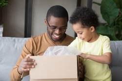 Happy black father and little kid son opening cardboard box looking inside, african american dad with cute child toddler clients receiving carton package, post mail parcel delivery service concept