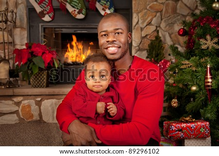 Happy Black Father and Son in front of Fireplace Decorated with Christmas Tree