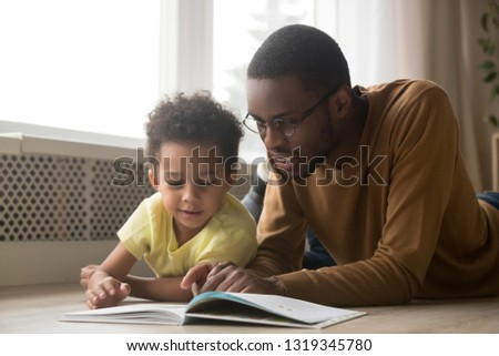 Photo of Happy black father baby sitter and toddler son having fun with book lying on warm floor, african dad teaching little kid boy learning to read, parent with children educational activities at home