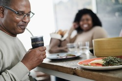 Happy black father drinking yerba mate during lunch at home - Main focus on man face