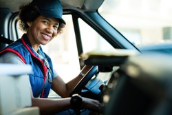 Happy black female courier driving delivery van and looking at camera.