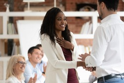 Happy black female employee get rewarded for professional achievement handshake boss, tolerant male manager shake hand of proud african business woman promote express recognition at work concept