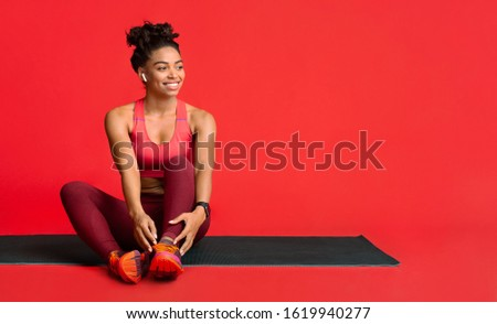 Happy black fitness girl resting on yoga mat during training, enjoying music with earbuds, copy space Stock photo ©
