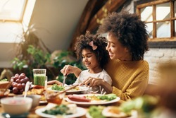 Happy black girl sitting on mother's lap while having a meal at dining table.