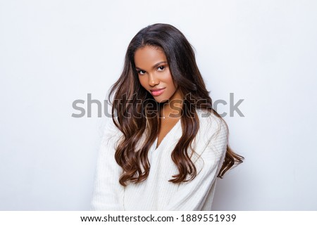Happy Black Girl Smile in White Sweater with long curly hair. Relaxed and Carefree. Portrait of beautiful black woman in white sweater with long curly hair