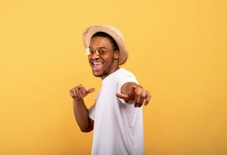 Happy black guy in casual summer outfit, straw hat and sunglasses pointing at you on yellow studio background. Positive African American man enjoying summertime, having fun